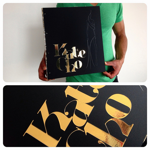 Custom matte black acrylic fashion design portfolio book with engraving and gold vinyl decal treatment