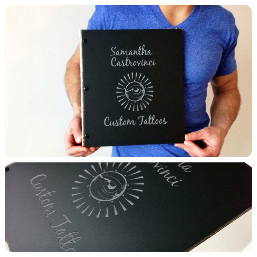 Custom tattoo portfolio book with engraving treatment on matte black acrylic